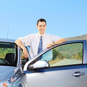 Smiling young male with tie posing next to his automobile on an open road